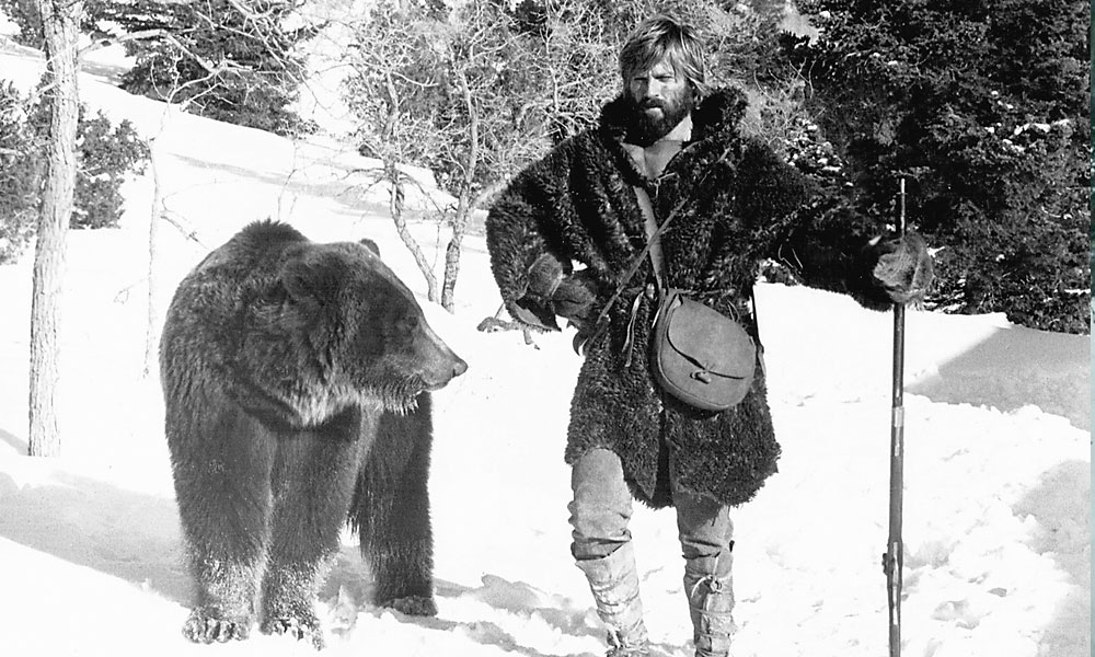 "Fraser Heston voted 1972's Jeremiah Johnson the best mountain man movie. Dan Haggerty concurs: ""Robert Redford did such a great job on it; no one could have done it better."" In the film, Redford's character (above) learns the basics of mountain survival from an older mountain man who specializes in hunting grizzly bears. – Courtesy Warner Bros. –"